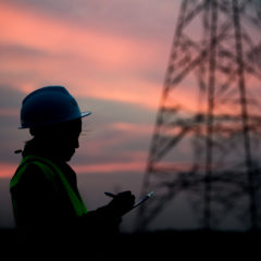 Worker by an electricity pylon