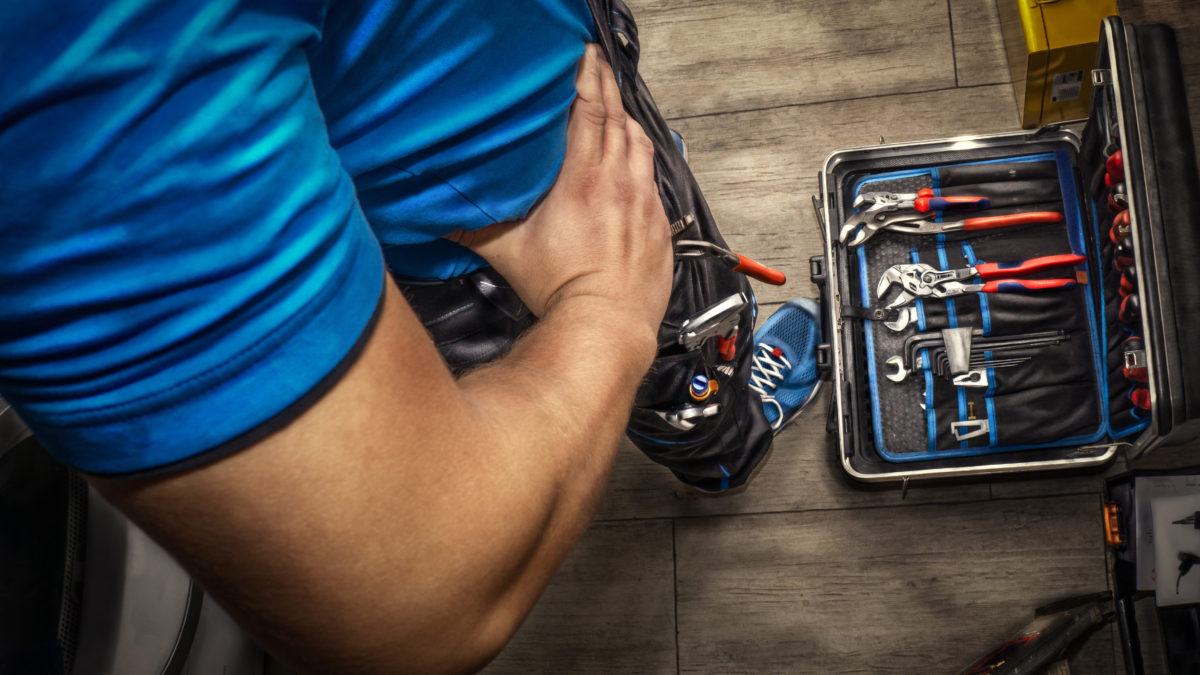 Image showing a box of tools at the feet of a self employed worker