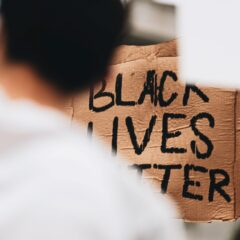 Someone holding a placard that reads black lives matter