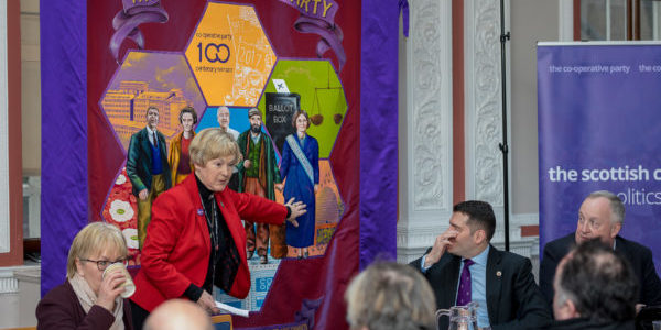 Scottish Co-operative Party Chair Rita Miller pointing to Mary Barbour on our banner